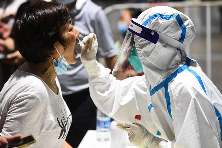 7月21日晚,在南京市玄武区一处检测点,医务人员在为市民进行核酸检测取样。