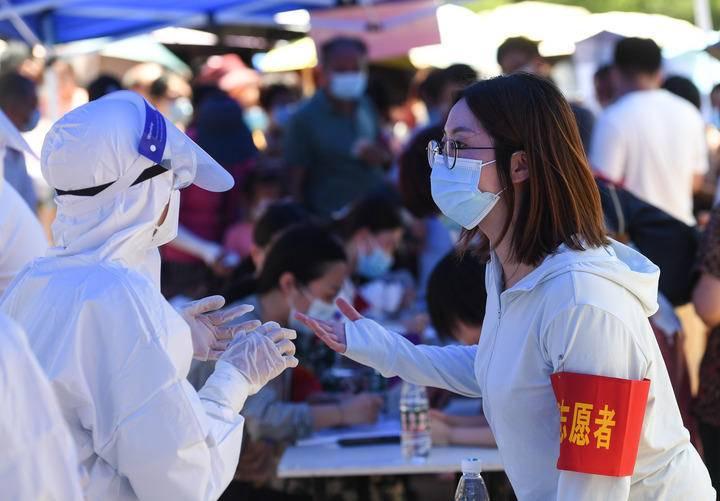 7月21日,在南京市江宁区万科·金域蓝湾小区检测点,江苏省中西医结合医院医生和社区志愿者交流。